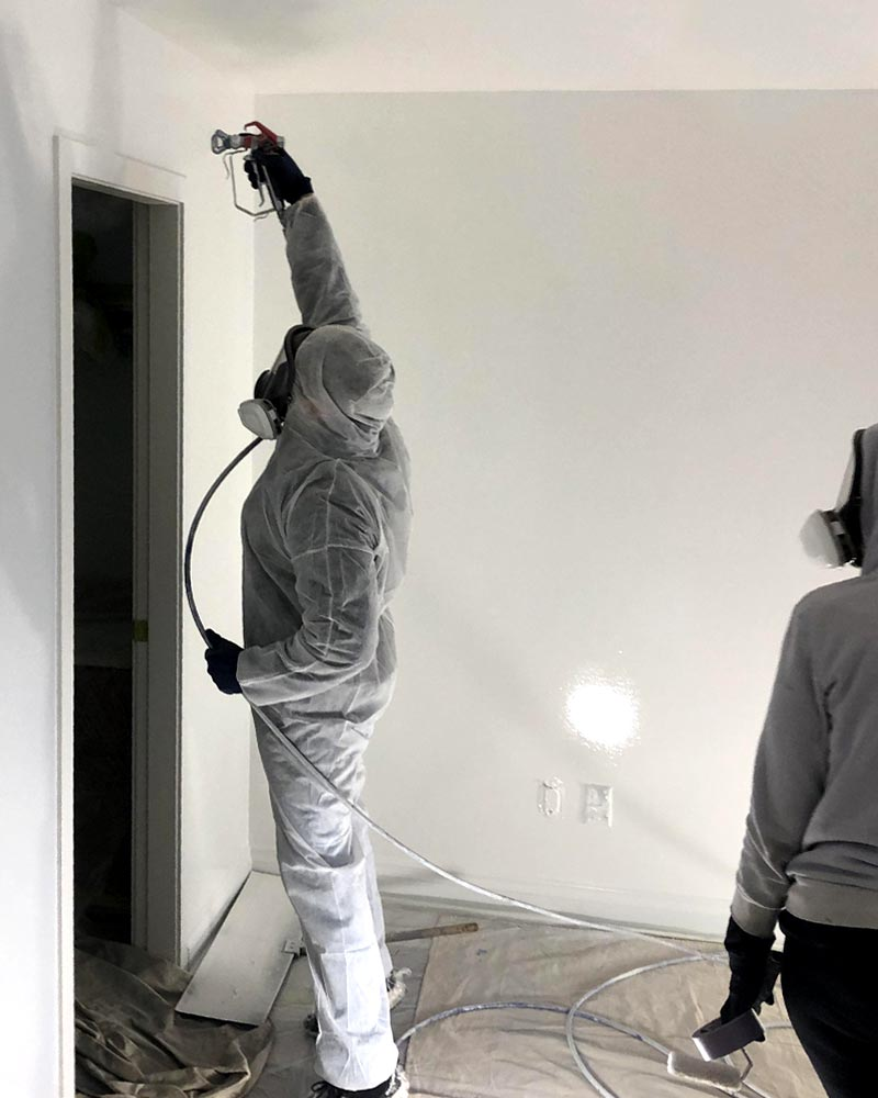 Watters Painting employees applying a white spray on paint to the inside of a house.