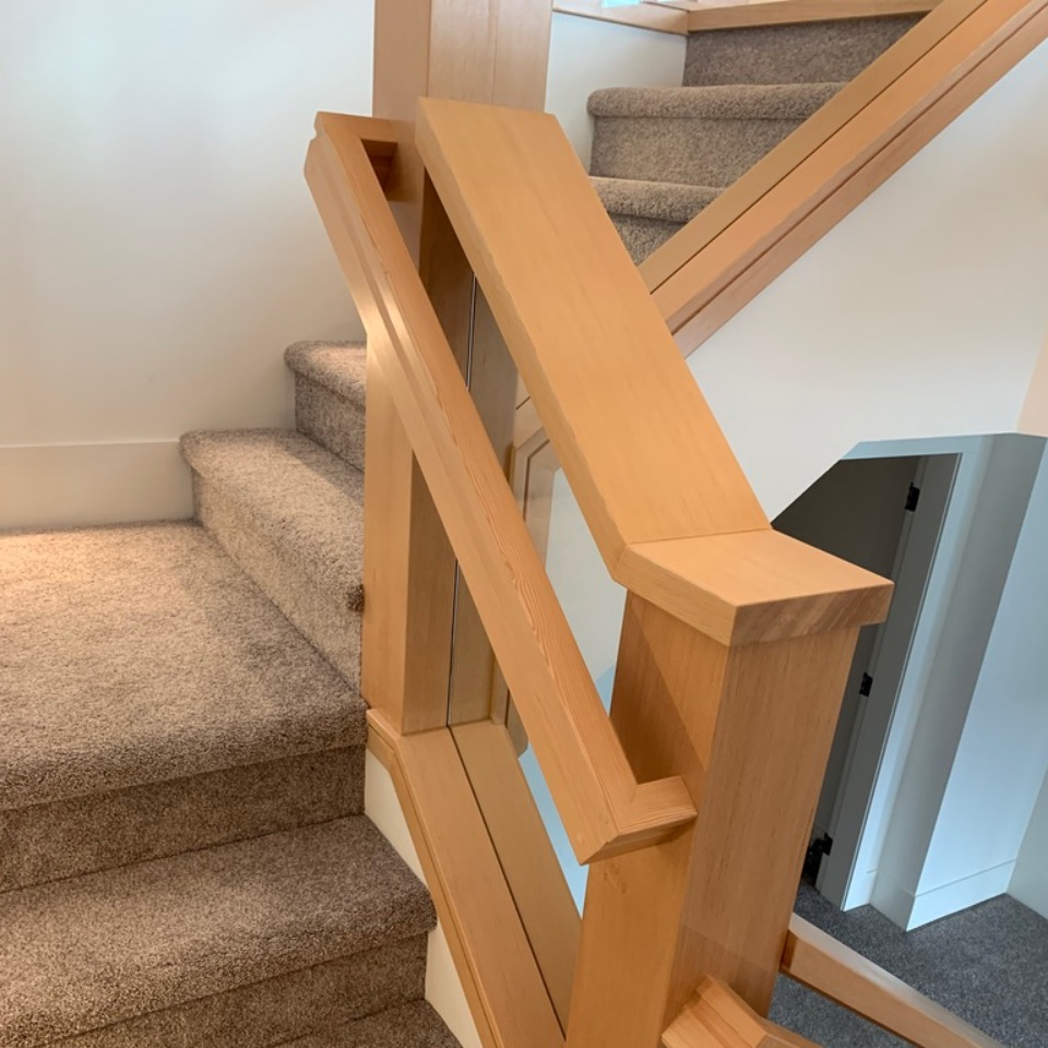 Closeup of a carpeted stairway with a wooden banister on the right.