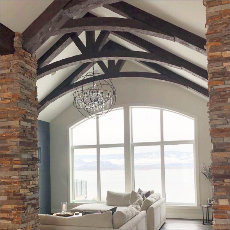 View looking into a living room with rock pillars on each side and wooden ceiling beams