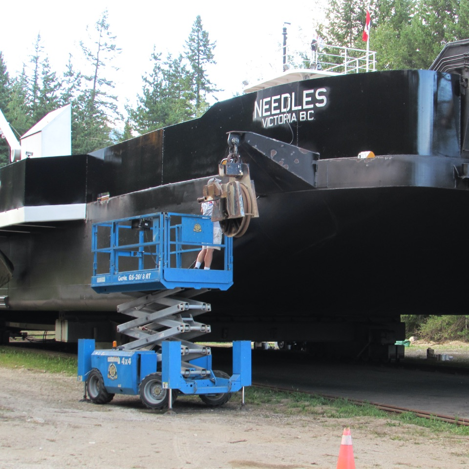 Closeup of a black ferry boat on land being worked on by a person on a scissor lift.