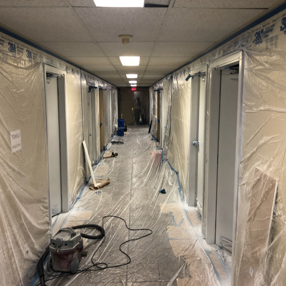 View looking down a hallways covered in protective plastic with tools laying on the floor and doors on each side.