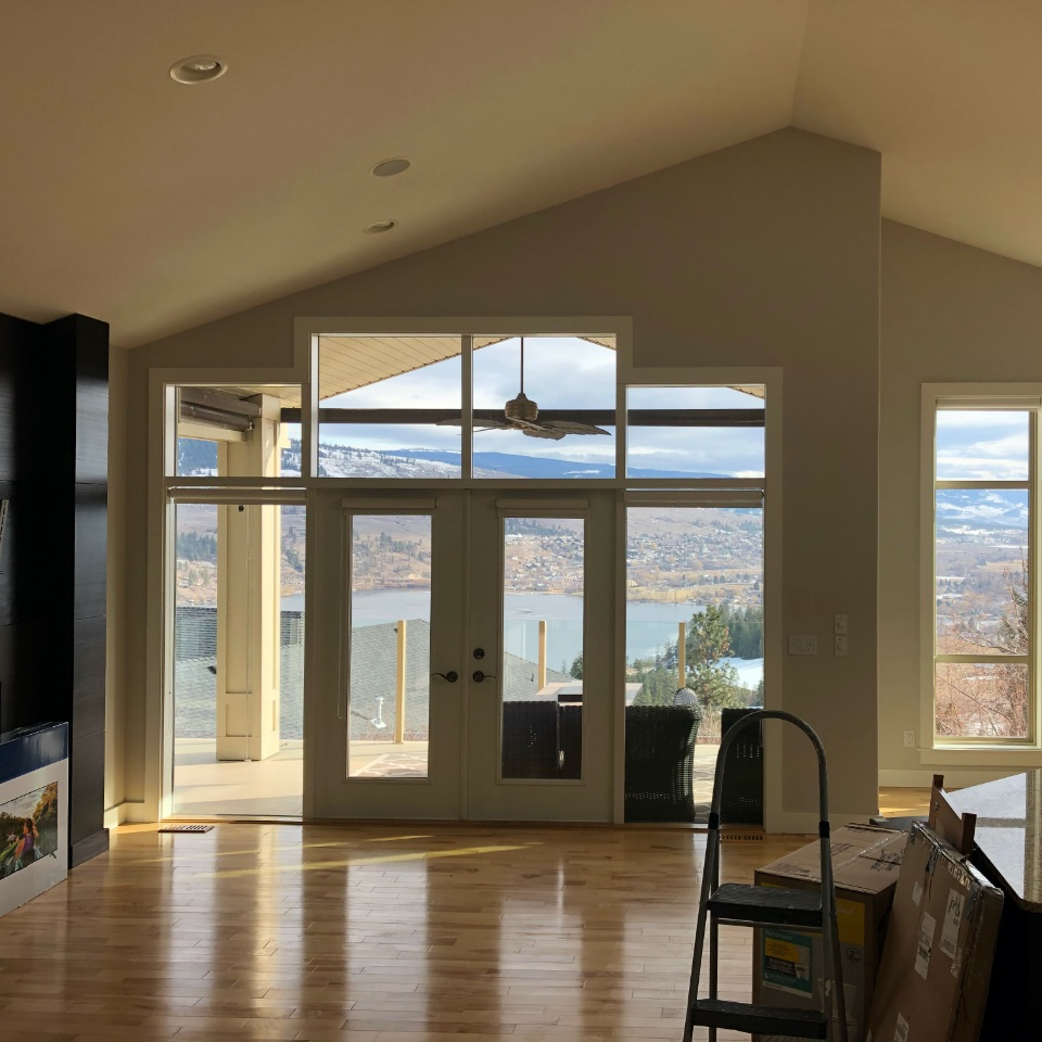 Living room with glass windows looking out towards Lake Okanagan.