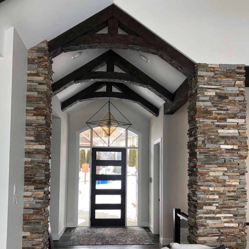 View of an residential house entry door form the inside with wooden ceiling support beams shown at the top. Image is in full colour.
