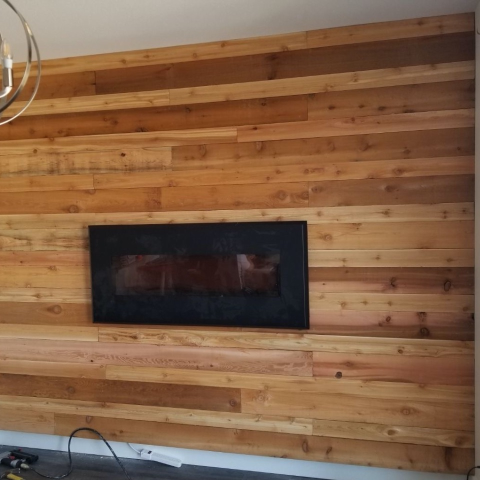View of a wooden wall with a wall mounted fireplace.