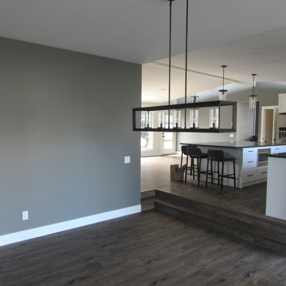 Empty living room with grey painted walls. Includes a kitchen in the top right corner and hanging lights.